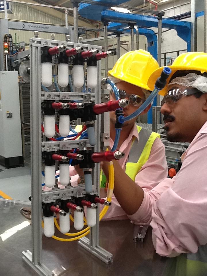 Operador capacitando a nuevo trabajador sobre técnicas de vacío para la industria.