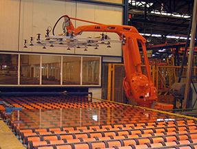 Robot naranja con gripper para tomar piezas de una banda trasportadora