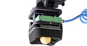 Un dispositivo KENOS con foami negro marca PIAB succionando una esfera naranja